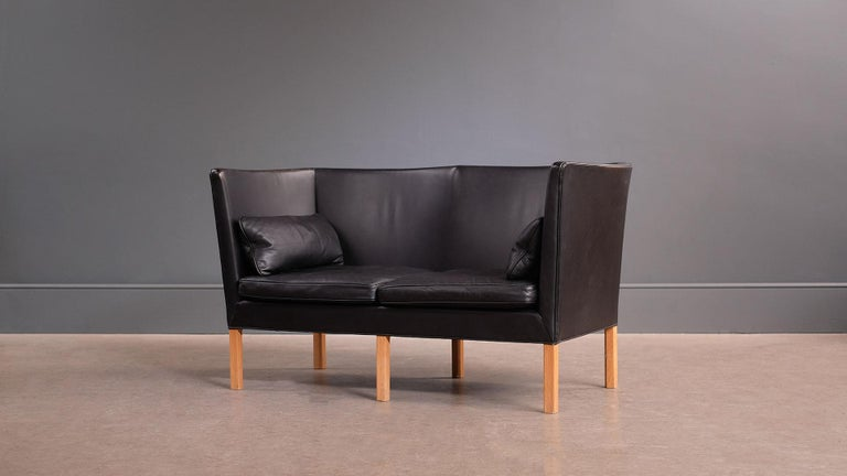 Ultra elegant sofa model 2214 designed by Børge Mogensen for Fredericia, Denmark, 1946. This example with beautifully patinated original black leather, oak legs and original accompanying pillows. Outstanding quality and super comfortable sofa.