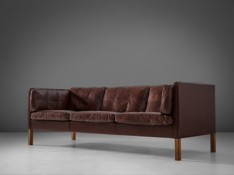 Børge Mogensen for Fredericia Stolefabrik, sofa model 2443, leather and oak, Denmark, 1960s.  This design comes from the 1960s and has wonderful shapes and comfort. The three-seater sofa comes with loose cushions in seating, back and sides. They