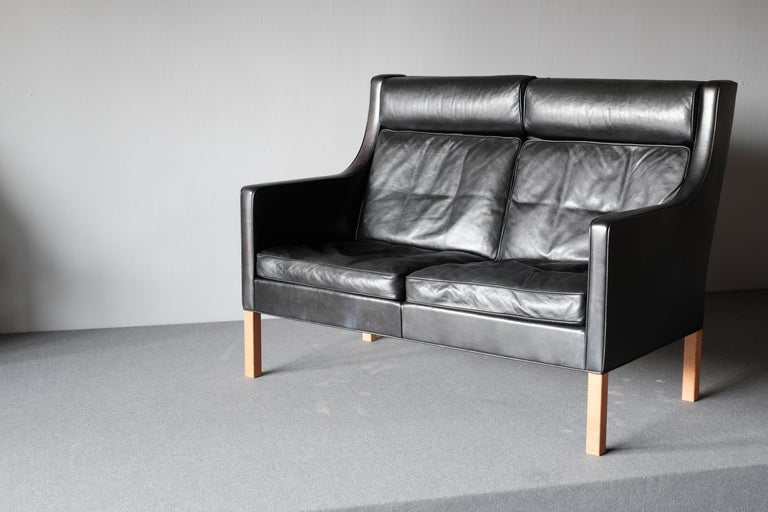 2-seat sofa by Borge Mogensen, manufactured by Fredericia. This model 2432 is upholstered in wonderfully patinated black leather and has legs in oak.   The wonderful quality of the sofa made from solid oak, upholstered in high grade leather and