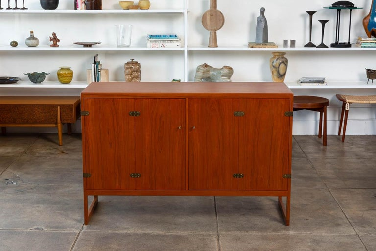 Børge Mogensen teak cabinet for Aalborg, Denmark, circa 1950s. The cabinet features a teak exterior frame and legs with white oak interior, patinated bronze hardware and folding door openings with adjustable shelving and drawers.  Condition: