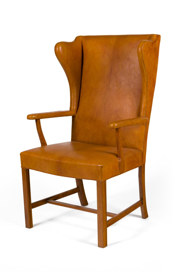 An extraordinarily rare and wonderful chair. Although similar in design to many of his wing chairs this chair has open arms that create a particularly graceful effect.