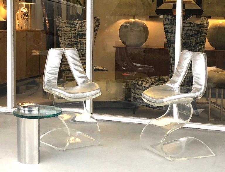 A wonderful pair of sculptural chairs. A single sheet of thick, clear Lucite manipulated into an artful practical piece of furniture. Retains the original silver faux leather upholstery.