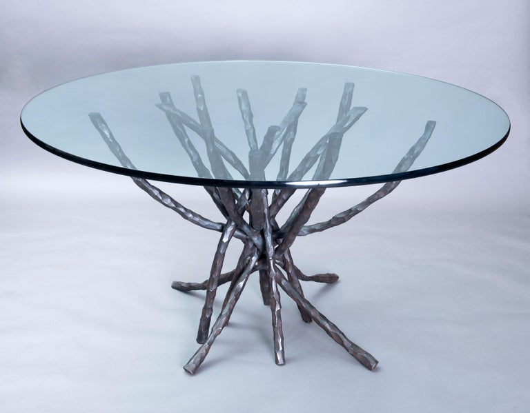 This one of a kind sculptural dining table in the round was handwrought from heavy solid bar stock. Heated and hammered and bent by hand each element is unique and welded in the center where the pieces intersect and coincide. The rich reddish brown