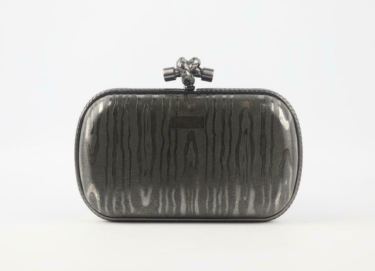 Bottega Veneta's 'Knot' clutch is such an enduring style, this Limited Edition clutch to celebrate the 50th Anniversary is crafted in silver with a signature gunmetal finish, the exclusive Moiré satin-silk effect confers a unique touch and