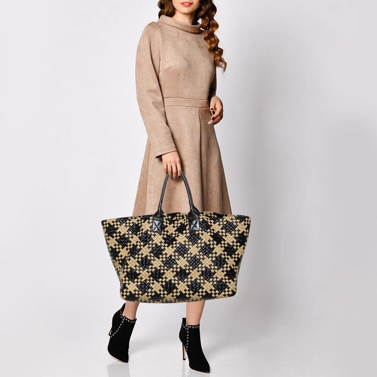 One look at this Cabat tote from Bottega Veneta and you'll know why it is luxe. Woven using black and beige leather in their Intrecciato technique and held by two rolled handles, it is brimming with artistry and quality craftsmanship. The bag is