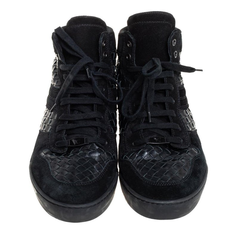 These stunning high-top sneakers by Bottega Veneta have been crafted from suede and leather. They come in a versatile shade of black and feature the brand's iconic Intrecciato weave. They come with a lace-up front, fabric lining, rubber, and leather