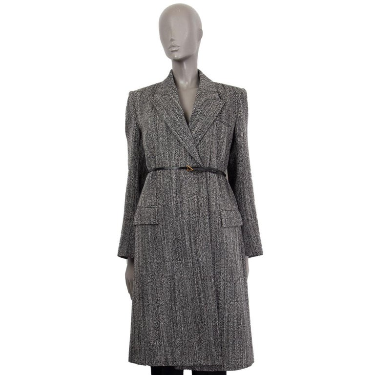 Bottega Veneta structured belted long coat in black and off-white wool (100%) with a peak collar, one chest pocket and two front flap pockets. Closes with a black leather belt with a gold tone triangular buckle. Lined in viscose (100%). Has been