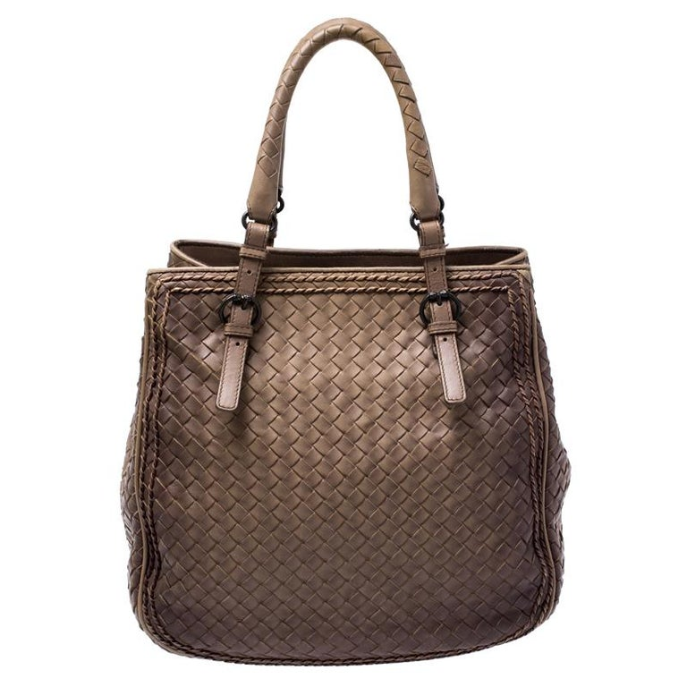 This bag from Bottega Veneta is crafted from brown leather using their signature Intrecciato weaving technique and flaunts a seamless design. This satchel, personifying elegance and subtle charm, is held by two handles. Brimming with artistry and