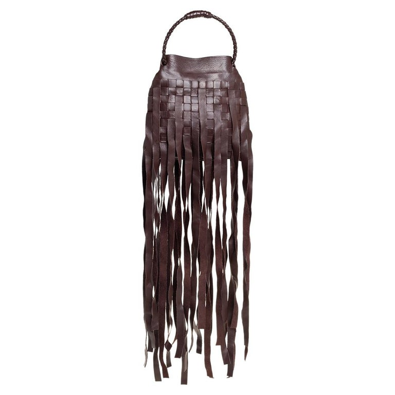 Brimming with artistry and quality craftsmanship, this pouch is a Bottega Veneta creation. Crafted from leather using their signature Intrecciato weaving technique, the bag is accented with fringes. The interior is compact and suede lined. This