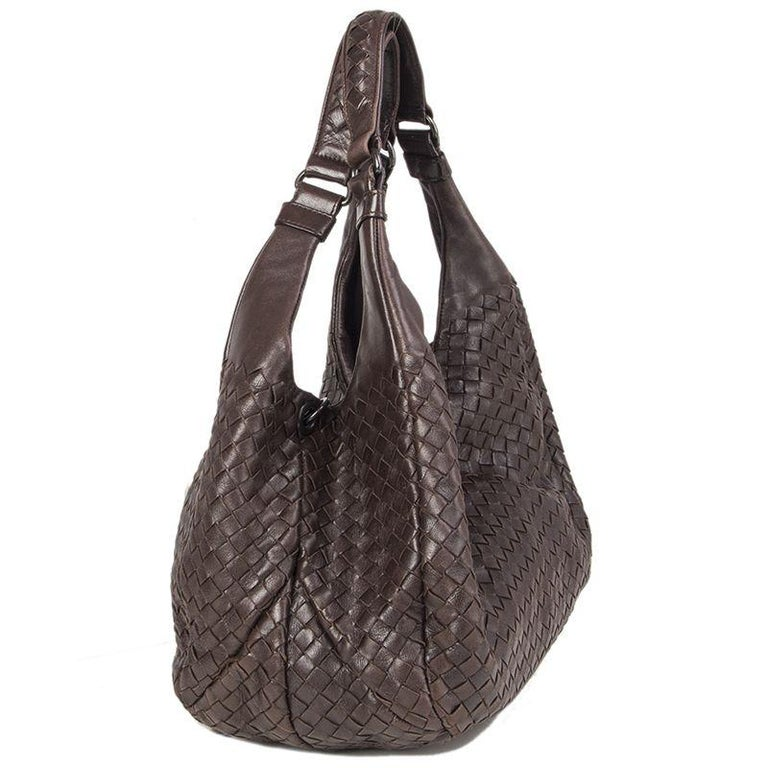 Bottega Veneta 'Campana Medium' shoulder bag in dark brown leather. Opens with a hidden magnetic button on top and is lined in beige suede with one zipper pocket against the back and a cell phone pocket against the front. Comes with a key strap