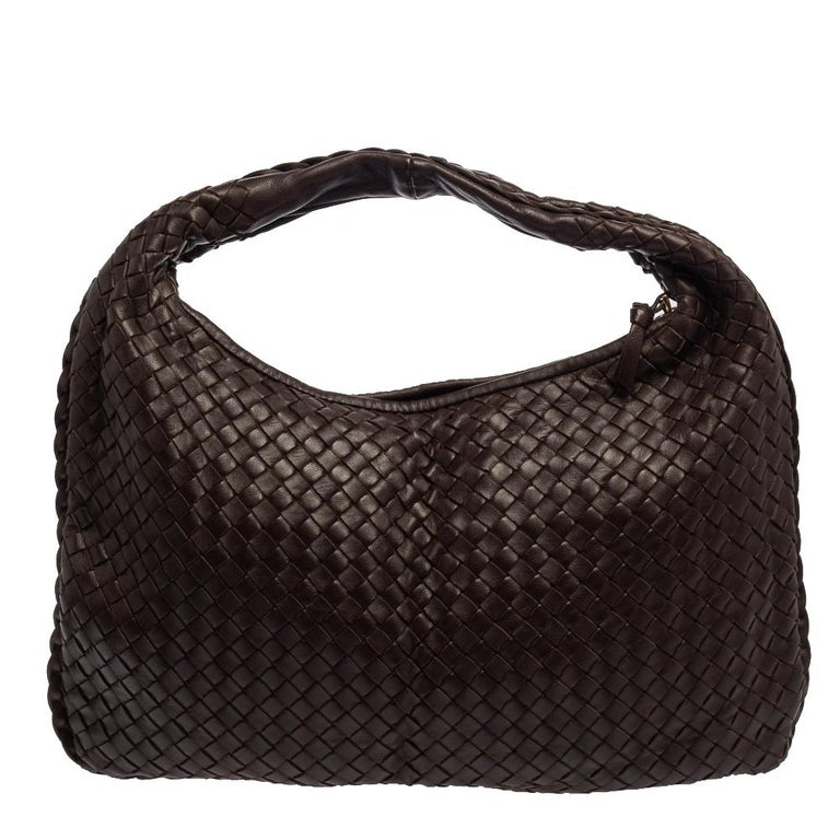 The excellent craftsmanship of this Bottega Veneta handbag ensures a brilliant finish and a rich appeal. Woven from leather in their signature Intrecciato pattern, the dark brown bag is provided with minimal gold-tone hardware. It features a loop