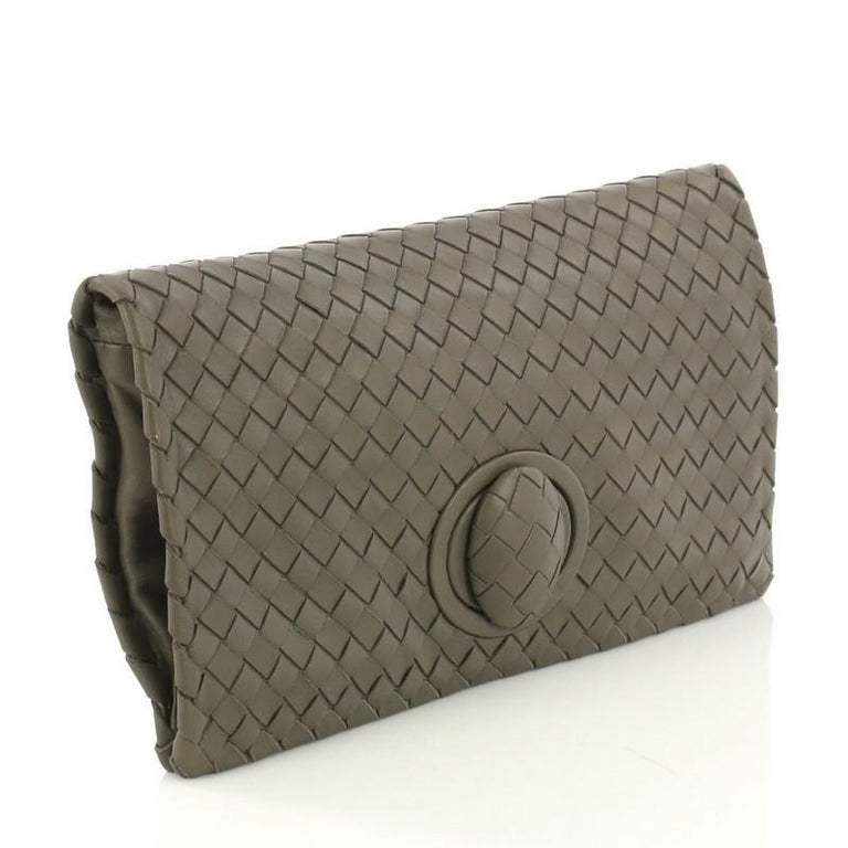 This Bottega Veneta Fold Over Turnlock Clutch Intrecciato Nappa, crafted from taupe intrecciato nappa leather, features a full fold-over flap and matte gunmetal-tone hardware. It's turn-lock closure opens to a taupe suede interior.   Estimated