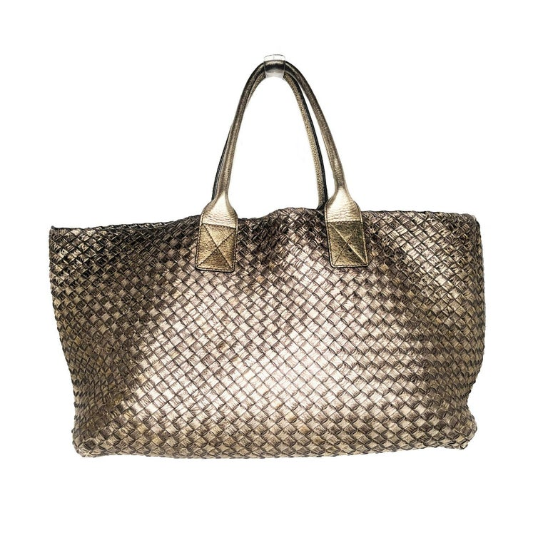 Metallic gold-tone Intrecciato Nappa leather Bottega Veneta Large Cabat tote with antiqued gold-tone hardware, dual rolled handles, tonal leather interior and open at top. Includes zip pouch.  Designer: Bottega Veneta Material: Intrecciato woven