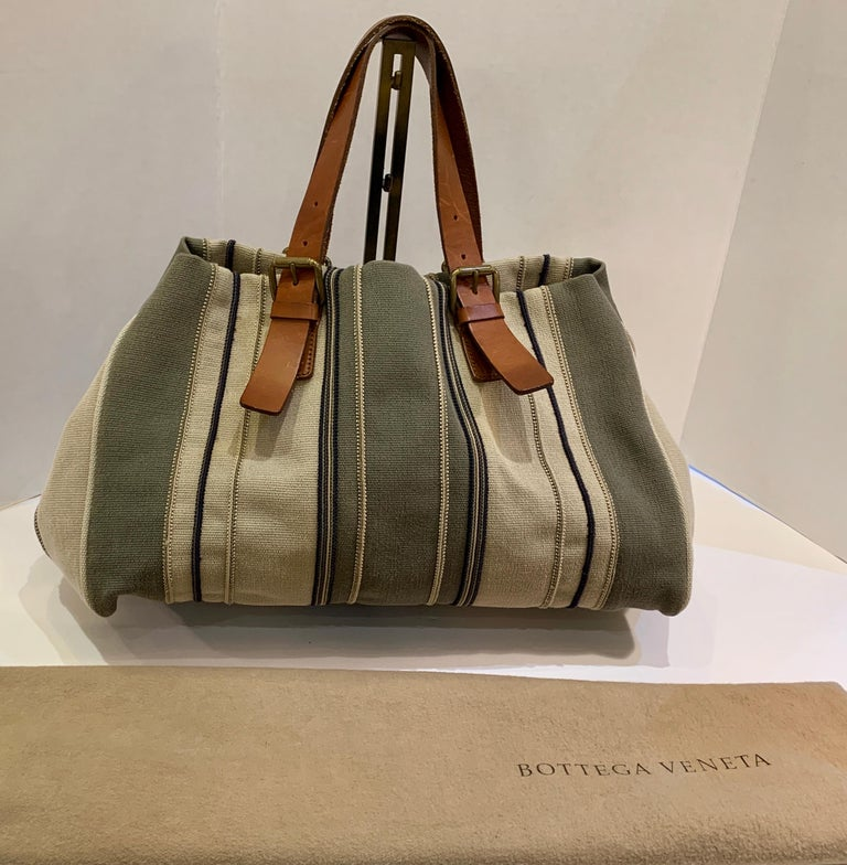 Bottega Veneta values quality craftsmanship, exclusivity and discreet luxury in the creation of its timeless handbags. This spacious, multi-colored, earth-toned striped canvas handbag or satchel features adjustable saddle colored distressed leather