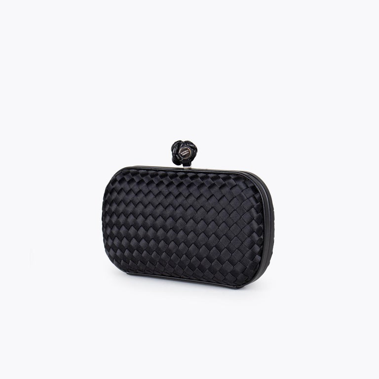 Black Intrecciato satin Bottega Veneta Knot clutch with  – Silver tone hardware – Tonal satin lining and push-lock closure at top  Overall Preloved Condition: Very Good Exterior Condition: Very Good. Minor surface scratches and marks