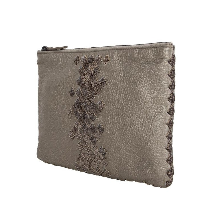 Bottega Veneta Intrecciato snakeskin pouch in meatllic grey with grey, taupe and black snakeskin details. Lined in taupe canvas. Brand new. Comes with dust bag.  Height 15cm (5.9in) Width 22cm (8.6in) Depth 1cm (0.4in) Blindstamp BO1300870F
