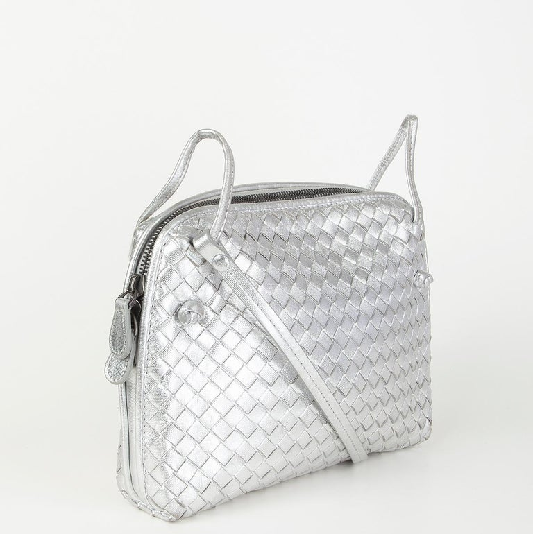 Bottega Veneta 'Nodini Small' crossbody bag in metallic silver Intrecciato. Opens with a zipper on topa nd is lined in dark taupe suede with one zipper pocket against the back. Has some faint wear to the corners and on the beginning of the shoulder