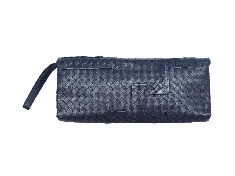 Product details: Navy Intrecciato leather rectangular clutch by Bottega Veneta. Wrist strap at side. 13