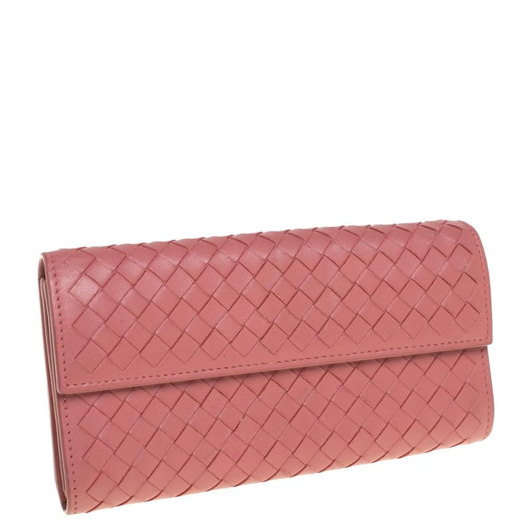 Covered in Bottega Veneta's iconic Intrecciato weave, this old rose wallet is instantly recognizable. A front flap closes securely with a snap lock. The wallet opens to show open compartments, a zipped pocket, and multiple card slots.