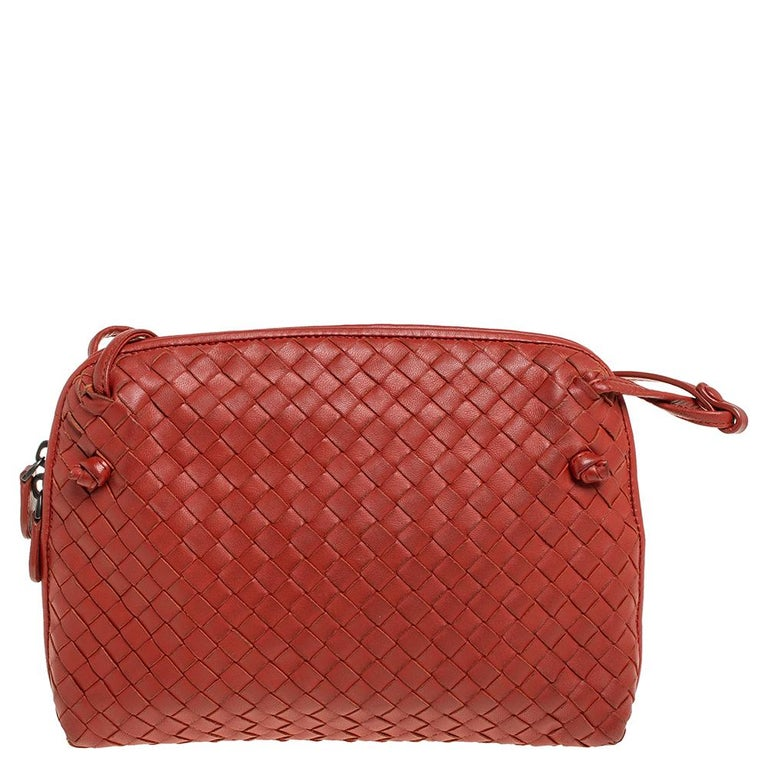 This Nodini bag from Bottega Veneta is crafted from orange leather using their signature Intrecciato weaving technique flaunting a seamless silhouette. This shoulder bag, personifying elegance and subtle charm, is held by a long shoulder strap.