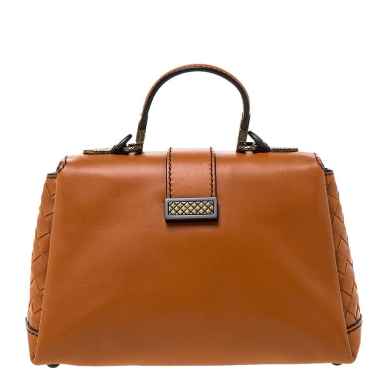This Bottega Veneta mini Piazza bag arrives in a structured shape and grand design. Crafted from orange leather, it has a press-lock on the flap, a top handle and a shoulder strap that is detachable. The flap secures a suede interior and overall,