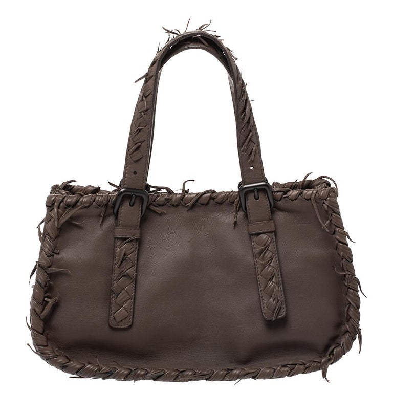 This sleek and spacious leather bag is luxurious enough to elevate any look. it is designed with intrecciato panels on the sides and bottom along with fringes on the outline as well as the handles. This bag has an inner lining of suede. Keep this