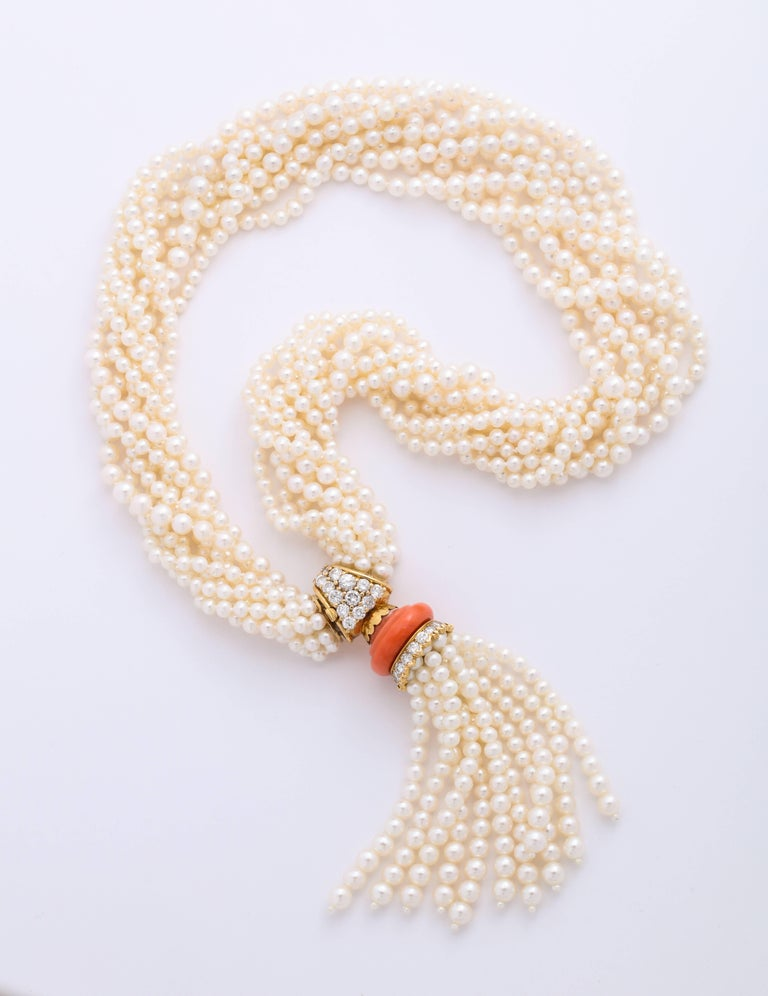 A multi-strand pearl torsad necklace set with a coral and diamond clasp, signed