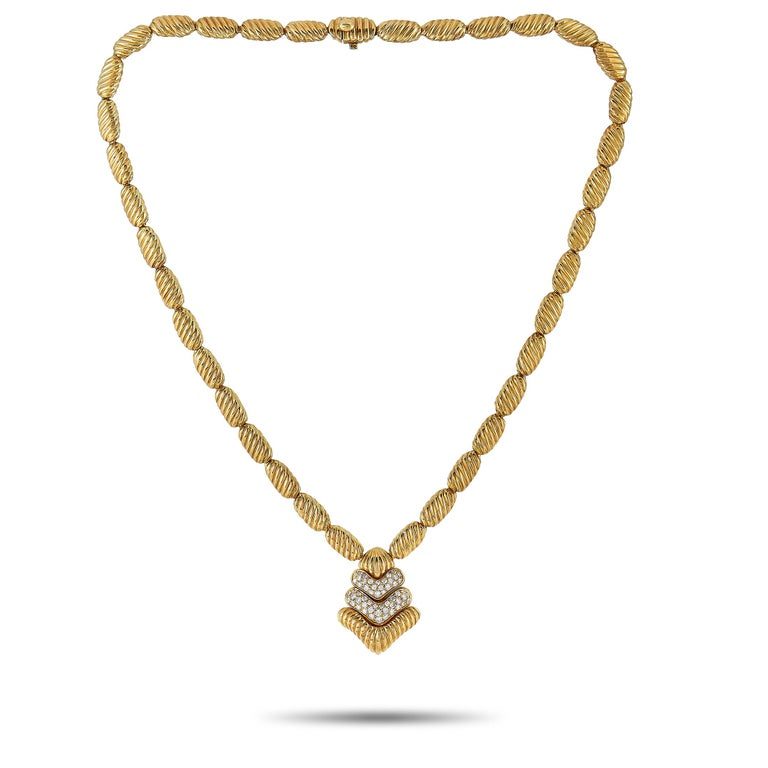 """This Boucheron necklace is crafted from 18K yellow gold and weighs 64.8 grams. It is presented with a 17"""" chain and a pendant that measures 1.12"""" in length and 0.80"""" in width. The necklace is embellished with diamonds that feature F color and VVS"""