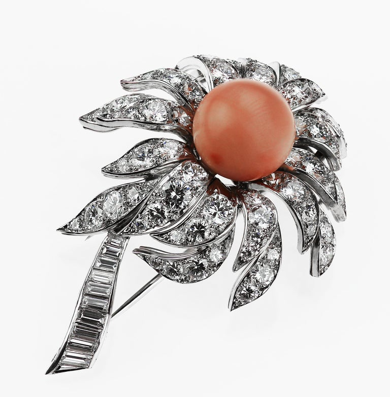 Stunning Boucheron 3D floral coral and diamond brooch circa 1980s consisting of a divine pastel pink coral centre with lengthy explosive diamond petals and a stem of baguette cut diamonds set in platinum.  Round brilliant and baguette cut diamonds,