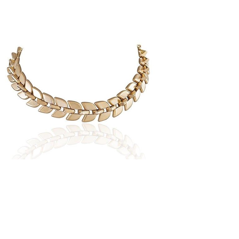 A French mid-20th century 18 karat gold necklace by Frederic Boucheron. The necklace, which elegantly and seamlessly breaks apart into two wearable bracelets, is comprised of highly polished rounded triangular section links, with two mirroring