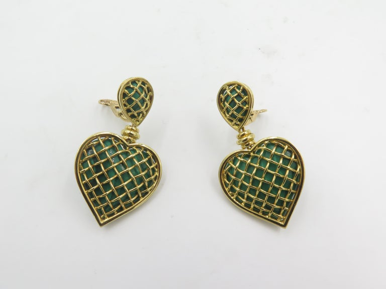A pair of 18 karat yellow gold and malachite earrings. Boucheron. French. Circa 1990. Each designed as a heart shaped malachite plaque, within a polished gold cage, suspending from a similarly designed tear shaped surmount. Length is approximately 2