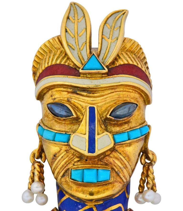 Featuring a tribal mask with channel set calibré turquoise and marquise cabochon sapphire eyes  Accented by red, white and blue enamel   Accompanied by articulated earring tassels terminating in round, natural, freshwater seed pearls  Completed by