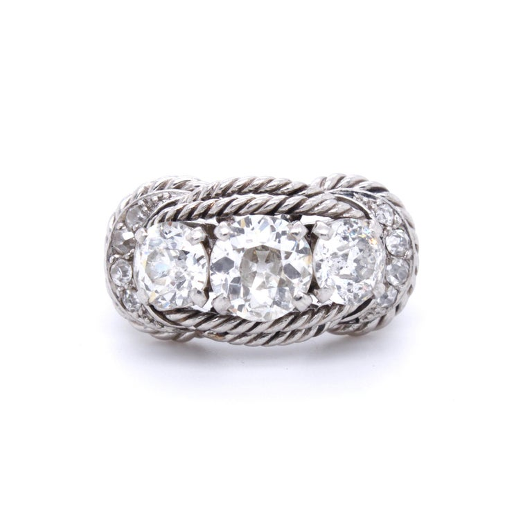 A chic Boucheron Retro Rope Three-Stone Diamond Ring, ca. 1940s  The ring has in the center an old-mine cut diamonds of ca. 1.1 carats (ca. I/VS), accentuated by two 0.6 carats (ca. I/SI) old-mine cut diamonds. The exquisite design with the fine