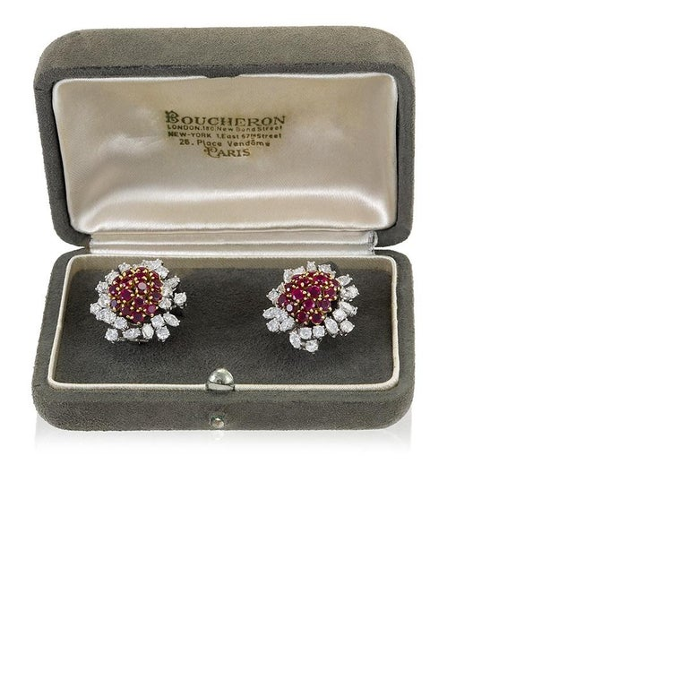 A pair of platinum- and gold-set diamond and ruby earrings by Boucheron. The earrings, housed in their original box from the mid-20th century, center on a semicircular raised cluster of remarkably well matched gold-set rubies. The tightly-nested