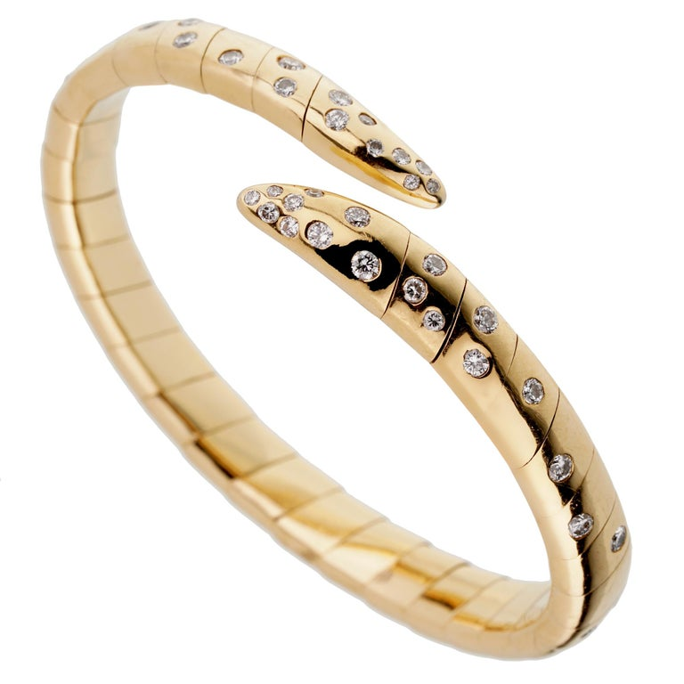 A magnificent Boucheron yellow gold bangle bracelet adorned with the finest round brilliant cut diamonds in shimmering 18k yellow gold. The bracelet has a weight of 56.4 grams and will fit a wrist of up to 7