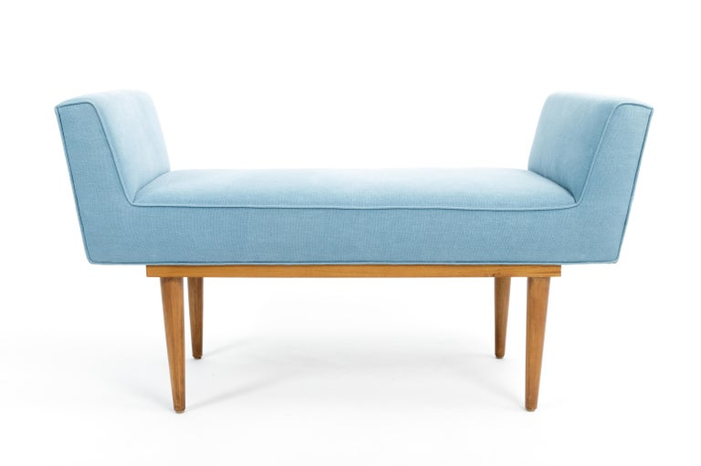Elegant mid-century boudoir bench, c. 20th century.   Simple yet sophisticated design consists of a handsome wood base and upholstered arms and seat. The bench in great vintage condition and has been newly recovered in a denim blue linen.