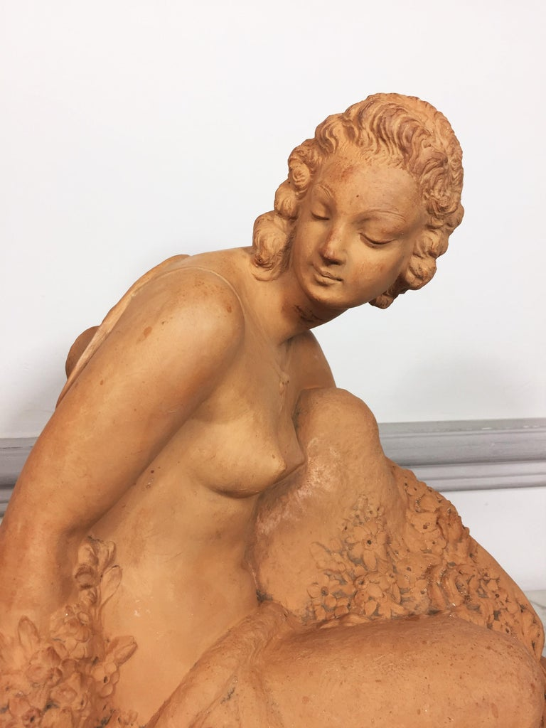 Very beautiful Art Deco terracotta by Marcel Bouraine depicting a denuded woman sitting on the floor holding flowers in her arms. Signature of the artist on the terrace.  Marcel André Bouraine (1886-1948) is a French sculptor born in Pontoise. He