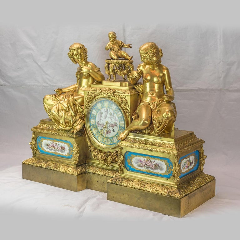 A Monumental Bourdin French figural gilt bronze mantel clock, depicting two women seated on the plinth with garland decoration and a cherub atop. Movement with rear plate stamped Bourdin A Paris and 3235.   Maker: Bourdin à Paris Origin: