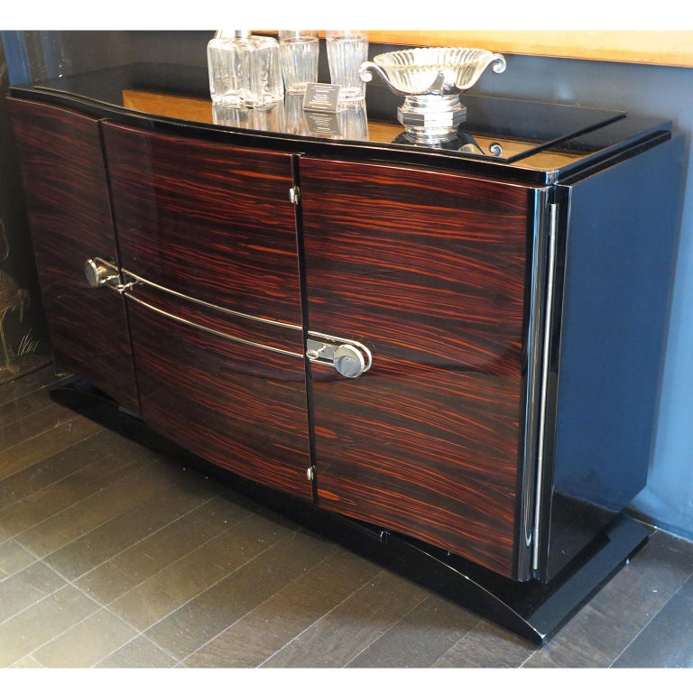 Smaller, elegant Art Deco sideboard with three Macassar ebony front doors. The bowed rectangular frame is entirely in black lacquer along with the base. The top has a thin black glass top. Original polished nickel hardware adorns the front doors.