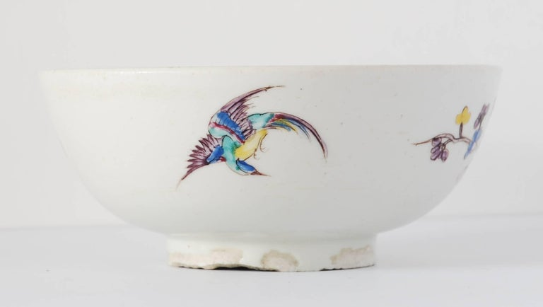 An early example of Bow porcelain, decorated in 'wet' famille rose colours; featuring a peony, a bird on a branch, and another in flight. Sacred Scrolls to the interior.  A superb example of early Bow.