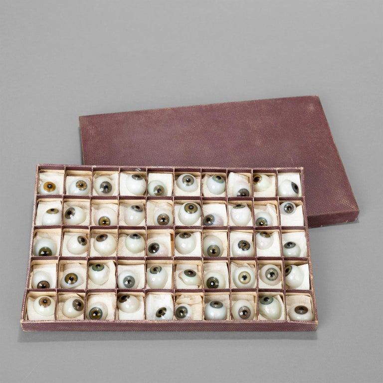 Prothestic blown glass eyes, presented in a cardboard box with individual compartments. Right or Left prothesis.  Box length 27cm, width 17cm, height 3 cm.