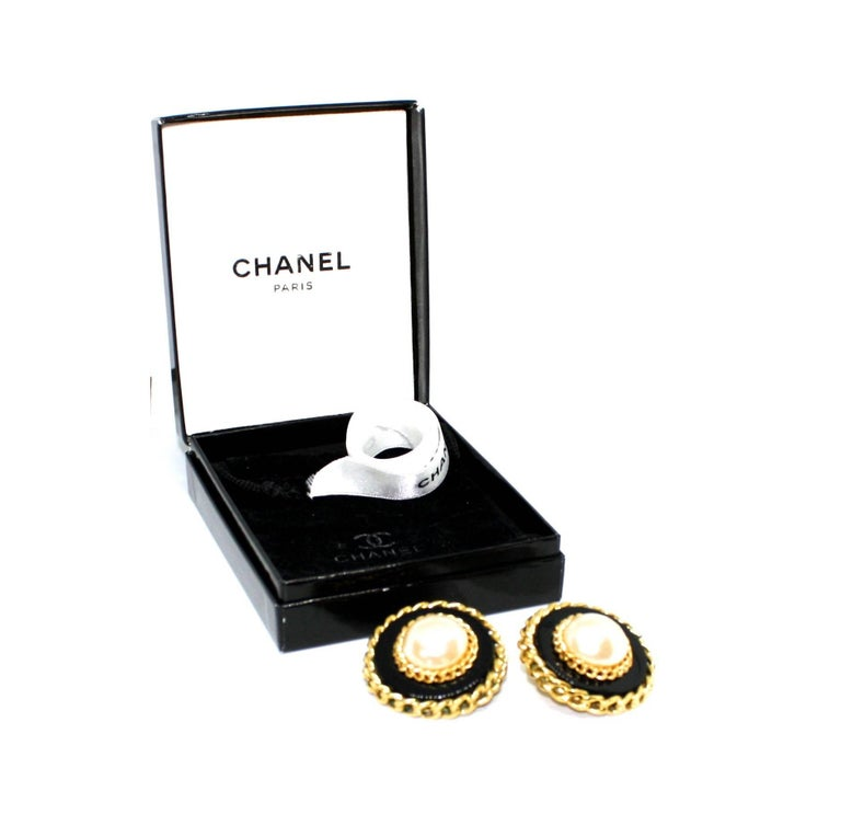 Iconic clip earrings by Chanel featuring a large central pearl surrounded by black acrylic and gold plated chains. Dated to the late 1980's/early 1990's, each earring is stamped with the Chanel Cartouche. The clip earrings are also provided with the