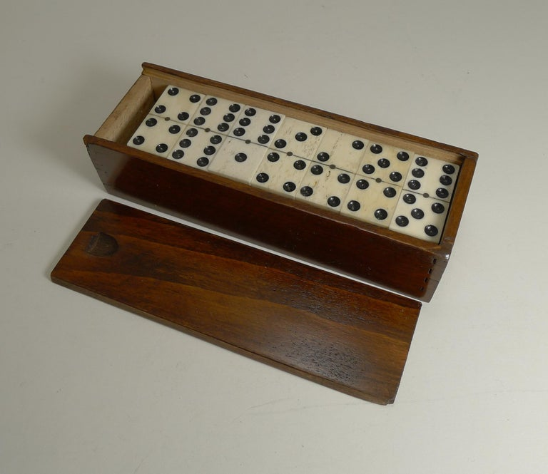 A charming set of late Edwardian dominoes or dominos, all in good condition with a handsome polished wooden storage box with a sliding lid.