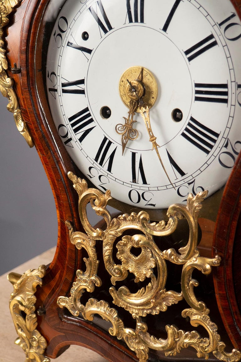 This clock exhibits the magnificent craftsmanship of the Italian Baroque. Guilloche decoration in gilt bronze emphasizes its luxurious curves and manages to make structural support seem feather light. The gently curved enamel clockface painted with