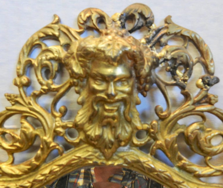 A lovely wall sconce by Bradley and Hubbard with a beveled mirror. There are two candleholders that have the holes drilled to add prisms if you desire. Ornate swirls form the frame for the mirror with a Greek God at the top. The brass is marked on