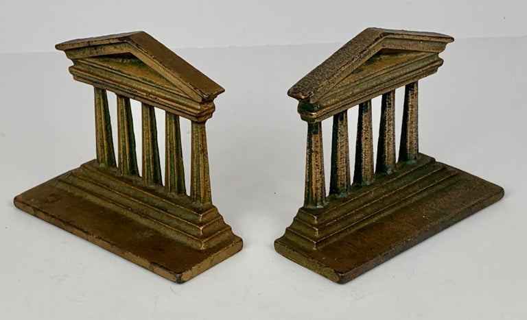 Pair of cast iron temple bookends by Bradley & Hubbard Manufacturing Company who operated in Meriden, Connecticut from 1852-1940. Nicely patinated and perfect for books on a desk or just neoclassical objects for any surface.