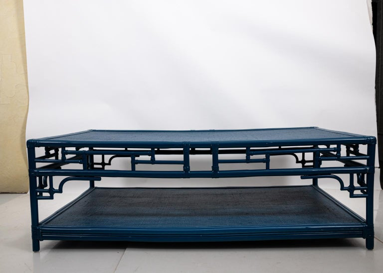 Blue painted, two tier braided Rattan and faux bamboo coffee in the Mid-Century Modern style, circa 1950s. Please note of wear consistent with age including minor wear and paint loss to the Rattan. Made in the United States.
