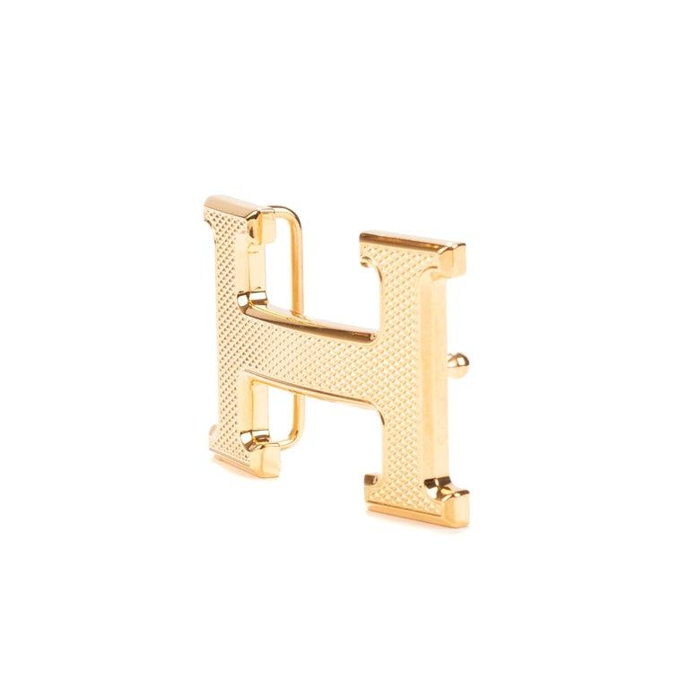 Type: Belt Buckle Marque: Hermès Modèle: Constance Guillochée Material : Steel Color : Gold Signature: HERMES  Shape : H For a leather of 3.2 cm. Dimensions : H: 3.7 x L: 6 x P: 1.4 cm Pristine condition - Never worn - Comes with dustbag