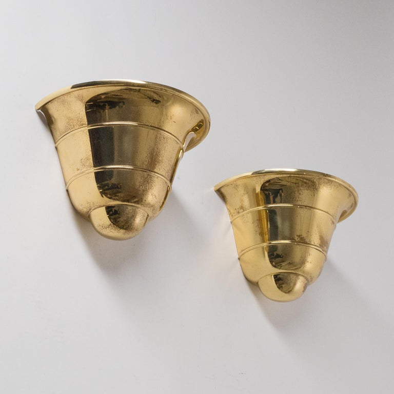 Rare pair of Art Deco brass upligth sconces by WMF Ikora, 1930s. Made from a single piece of brass with a tiered silhouette. Nice original condition with patina and one original brass and ceramic E27 socket each. Manufacturers stamp on each