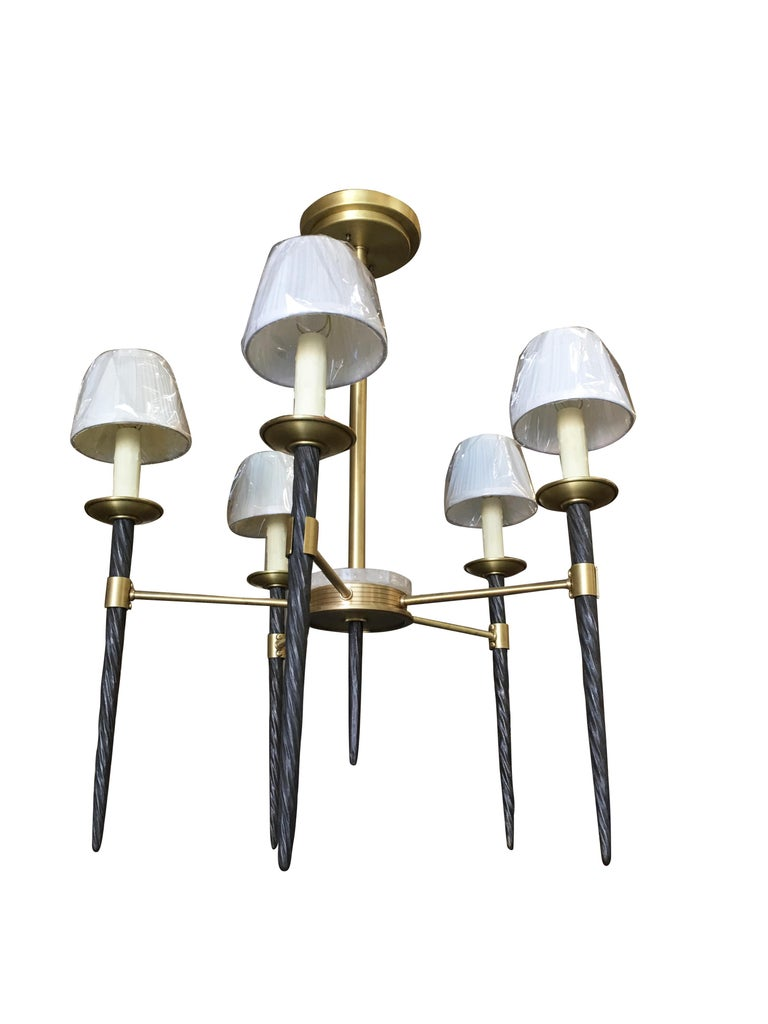 High style brass chandelier with 5 lights sitting on Narwhal Tusks toped with fabric lamp shades and a rock crystal center cap.